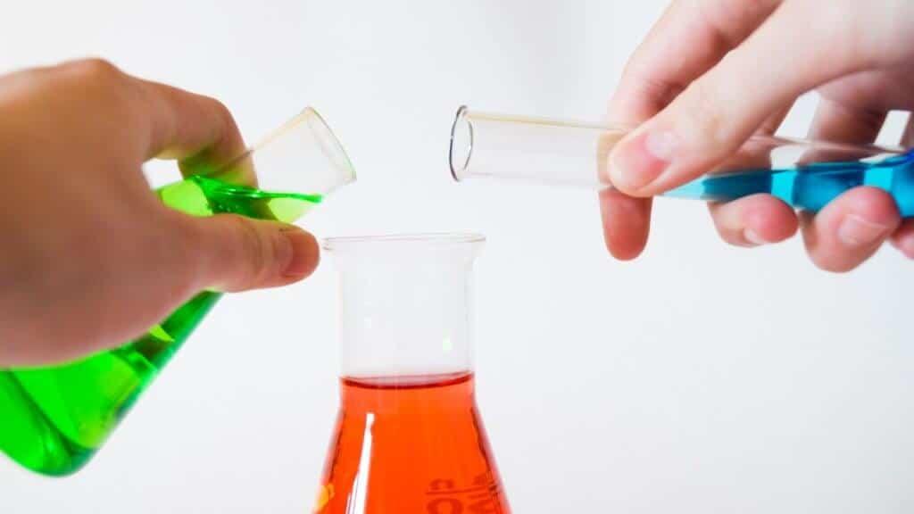 Photo de deux mains qui ajoutent une solution à une autre solution chimique