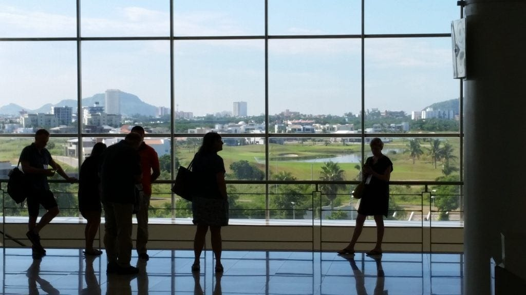 silhouettes of business people at floor to ceiling window in Mazatlan's International Convention Center