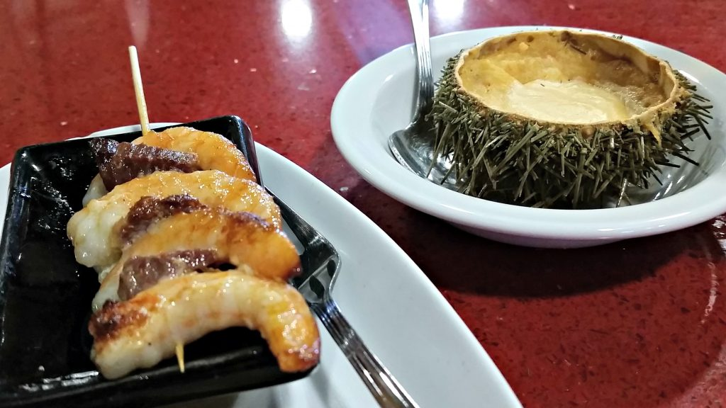 San Sebastian food including a bowl of croute served in a sea urchin and a skewer of three shrimps with ham
