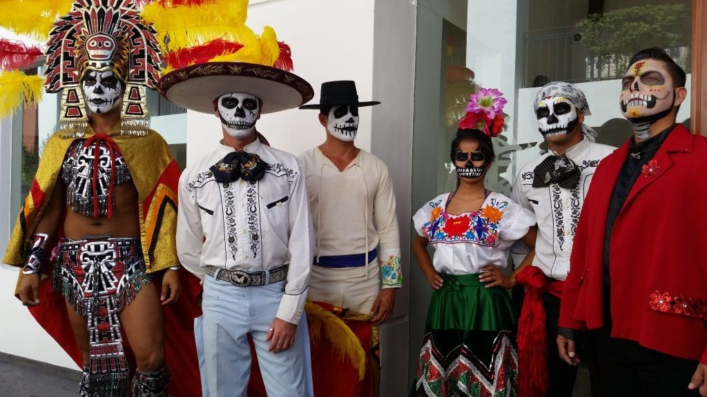 Men and one woman with faces painted white and skeleton eyes, noses and teeth painted, dressed in Mexican and Aztec regalia