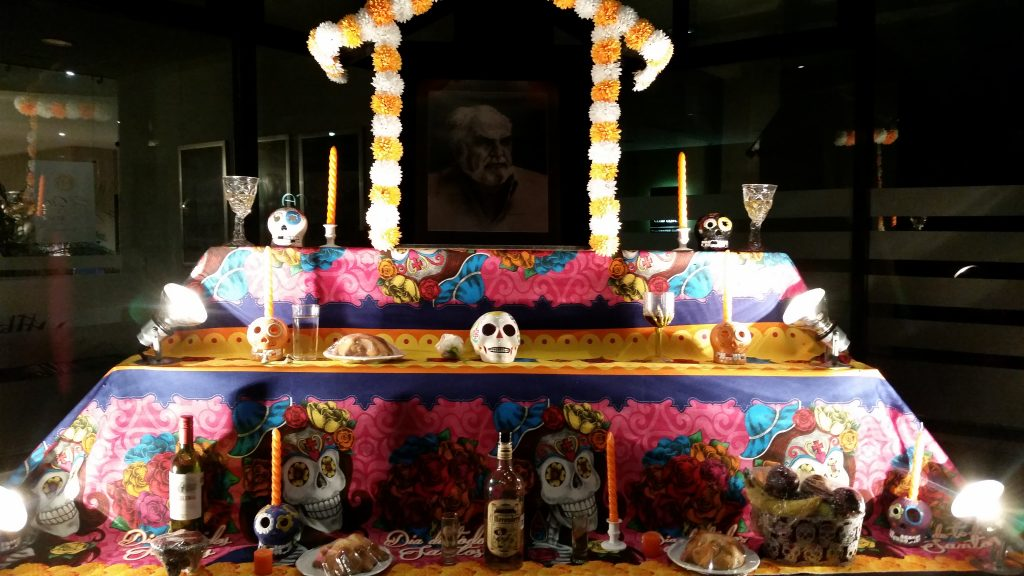 Offrenda or altar decorated in festive pinks and yellows with skulls, food, candles and bottles of tequila