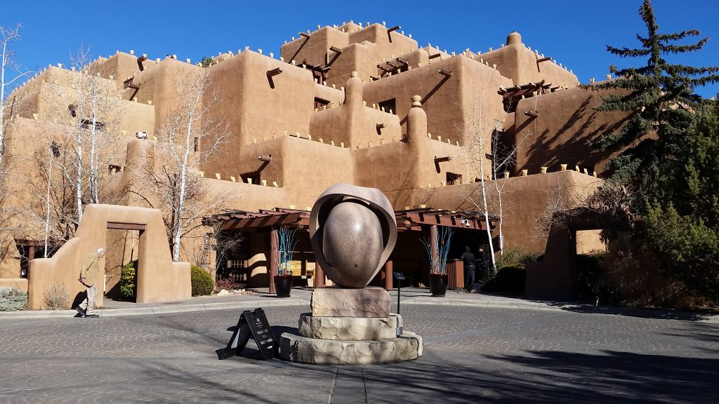 Exterior of six-story hotel designed after traditional pueblo with multiple flat roofs, log beams (vigas) sticking out of adobe-like walls. New Mexico blue sky behind.