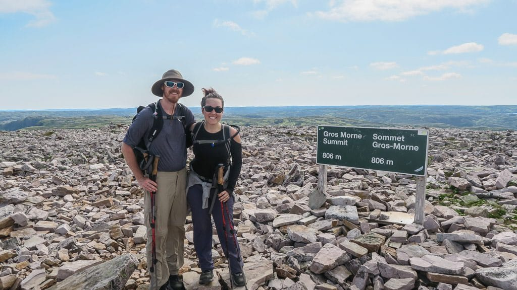 Brooke and Buddy posing at the Gros Morne Mountain Summit sign with an altitude of 806m
