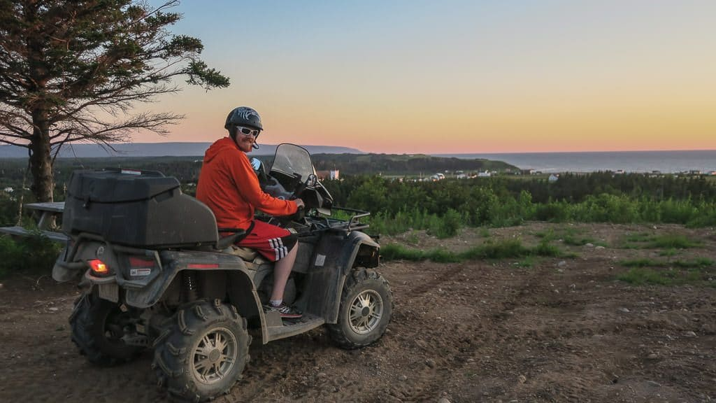 Buddy sitting on the ATV while the sun sets behind him