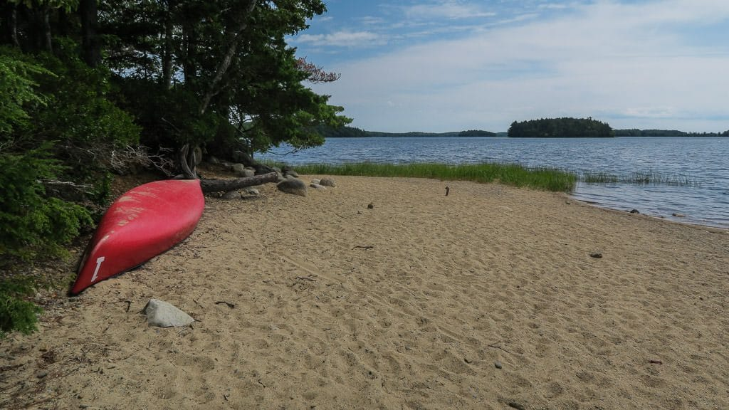 Canoe sitting in the sand at one of the beaches in kejimkujik national park