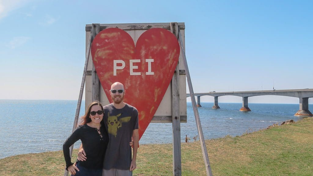 Brooke and Buddy taking a photo next to the PEI sign before crossing Confederation bridge to leave Prince Edward Island