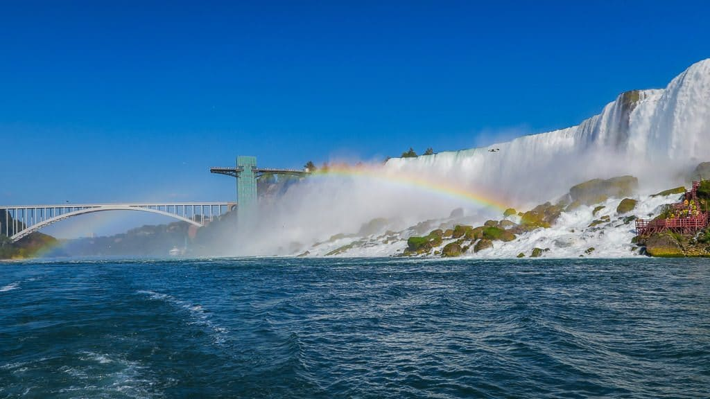 Niagara Falls from our hornblower cruise, looking back towards the pedestrian Rainbow Bridge, with a rainbow next to it.