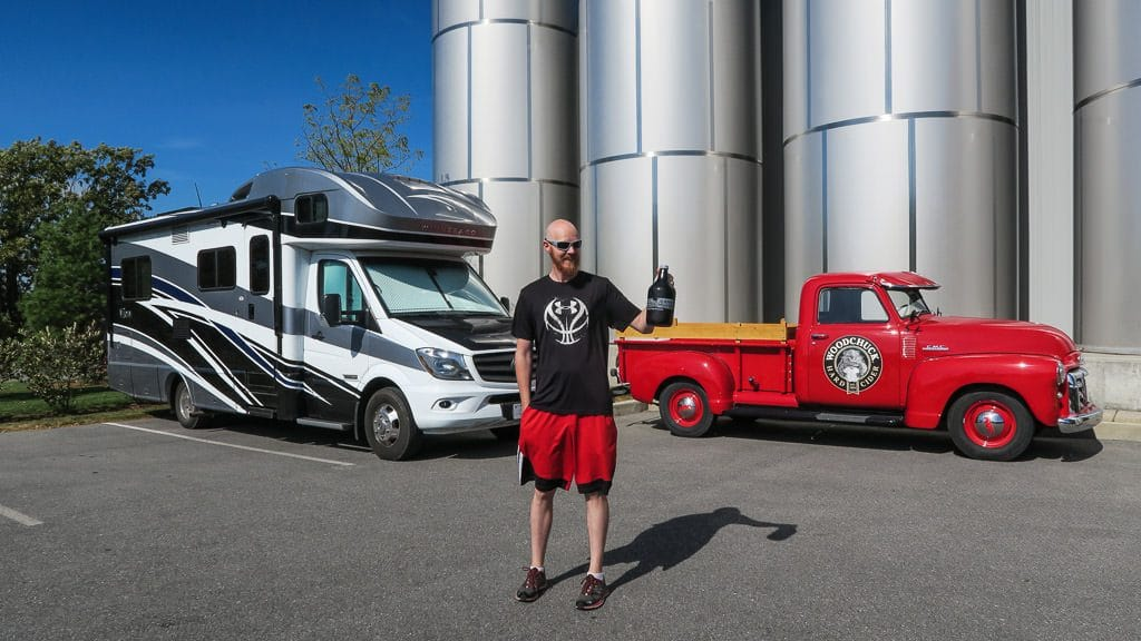 Buddy standing in front of our RV holding a growler full of cider at Woodchuck Cidery in vermont