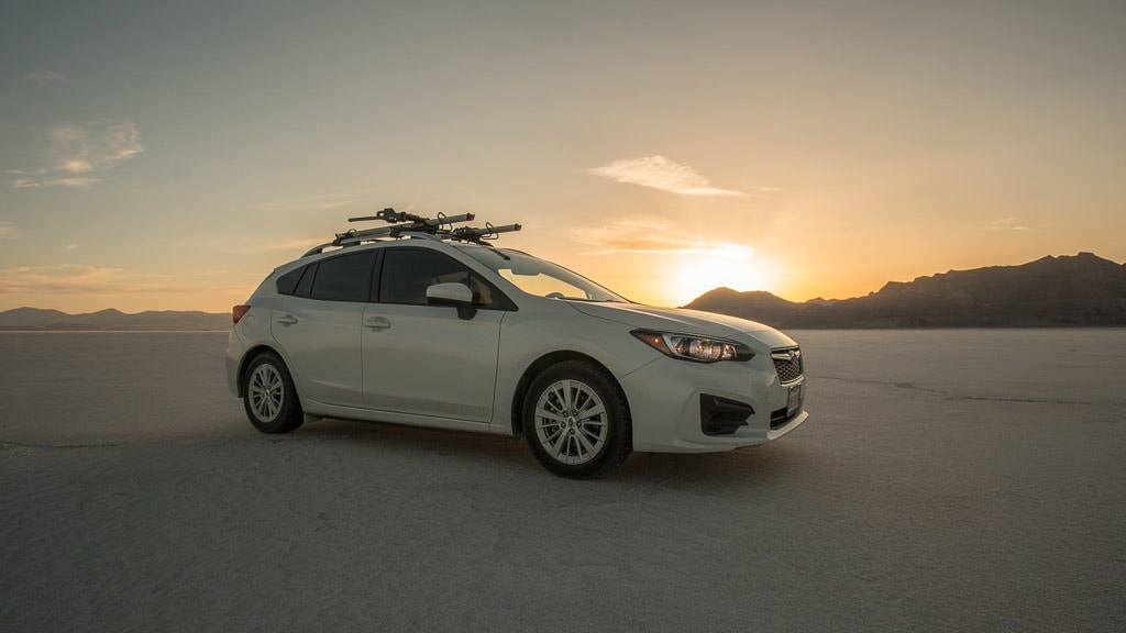 Our Subaru on the Bonneville Salt Flats with the sun setting behind the mountains in the background