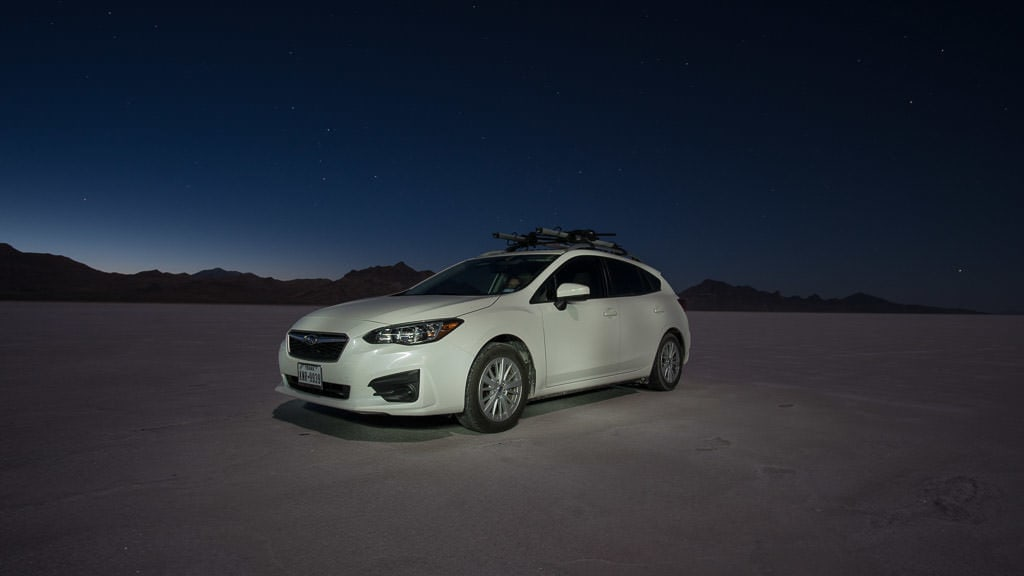 Our Subaru on the bonneville salt flats at night with stars in the sky and the silhouette of the mountains in the background