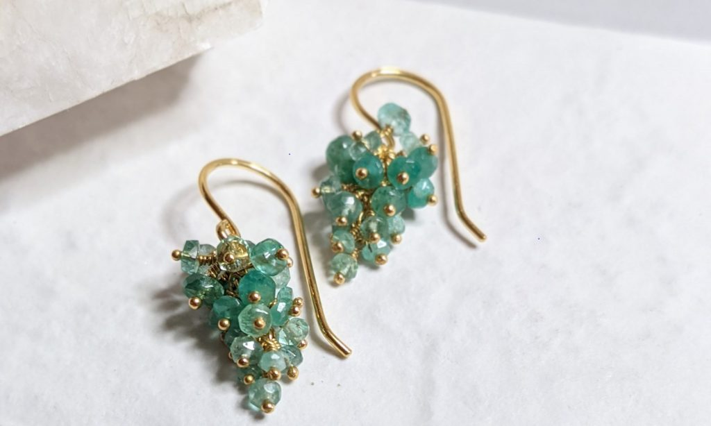 Emerald Beaded earrings on a textured white background