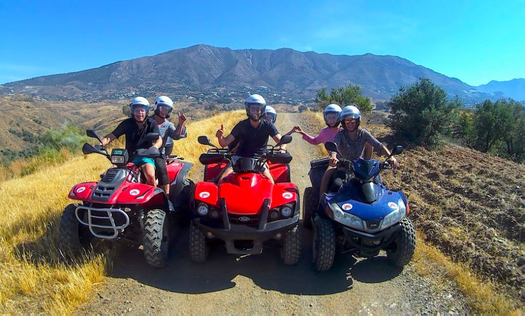 3 quad bikes against a stunning mountains with riders thumbs up