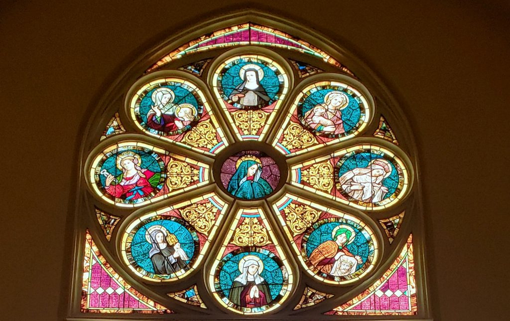 rose window of red and blue glass on the Wisc Way pilgrimage depicting women saints