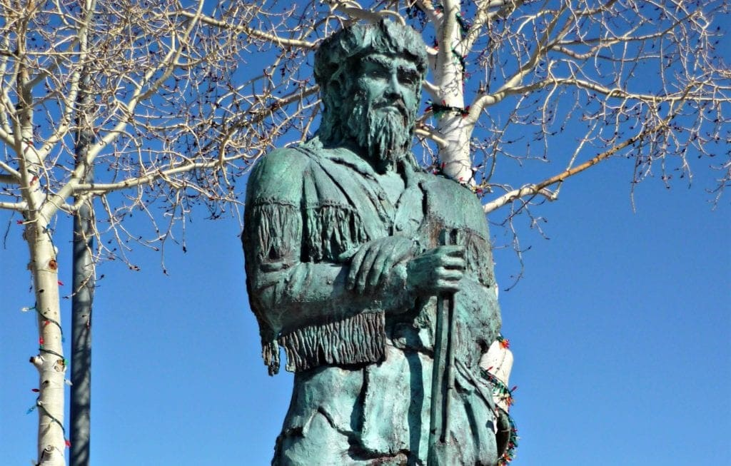 bronze scultor of man dressed in buckskins and holding a rufle is Bill Williams found on Route 66 in Arizona