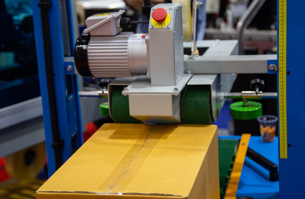 Case sealer seals a cardboard box as part of the packaging line process