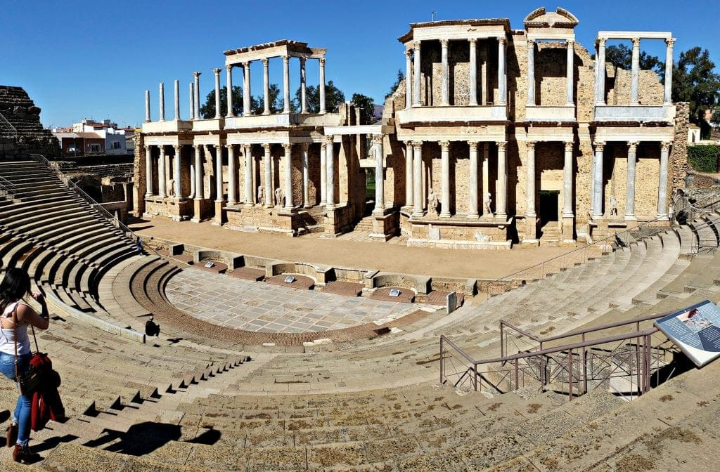 White marble columns of the Roman Theatre are shown from the seating area above. One lone woman experiences the semi-circular outdoor space.