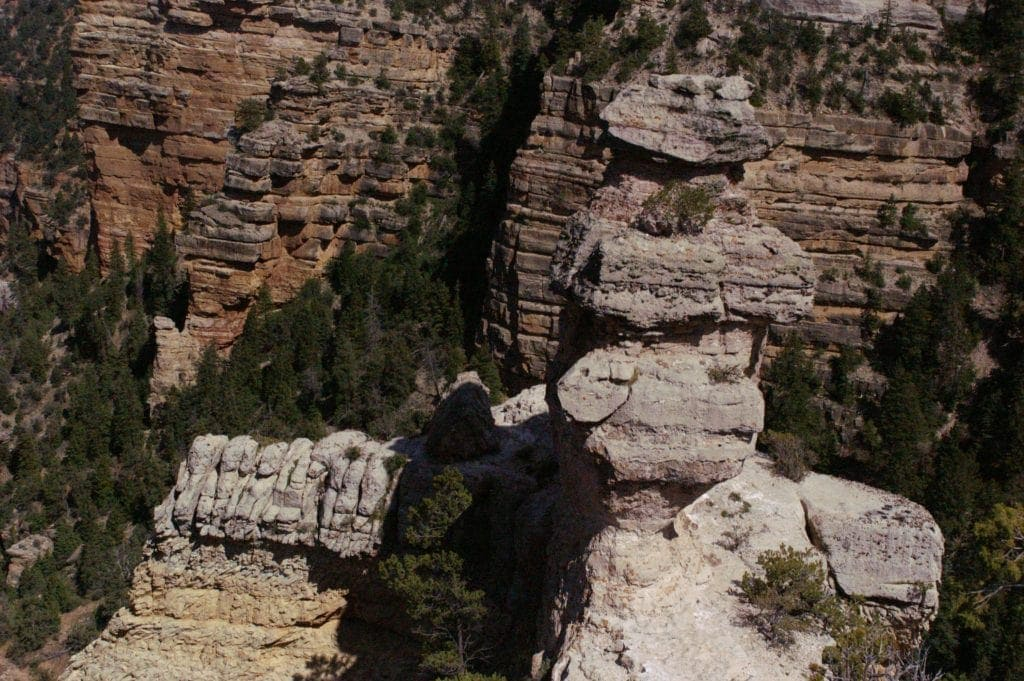 While limestone formation in the shape of a duck sits atop edge of Grand Canyon South Rim