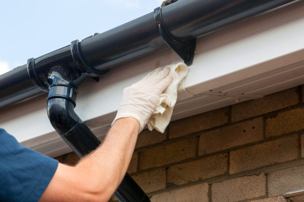Roofing Inspector cleaning house fascia boards and gutters