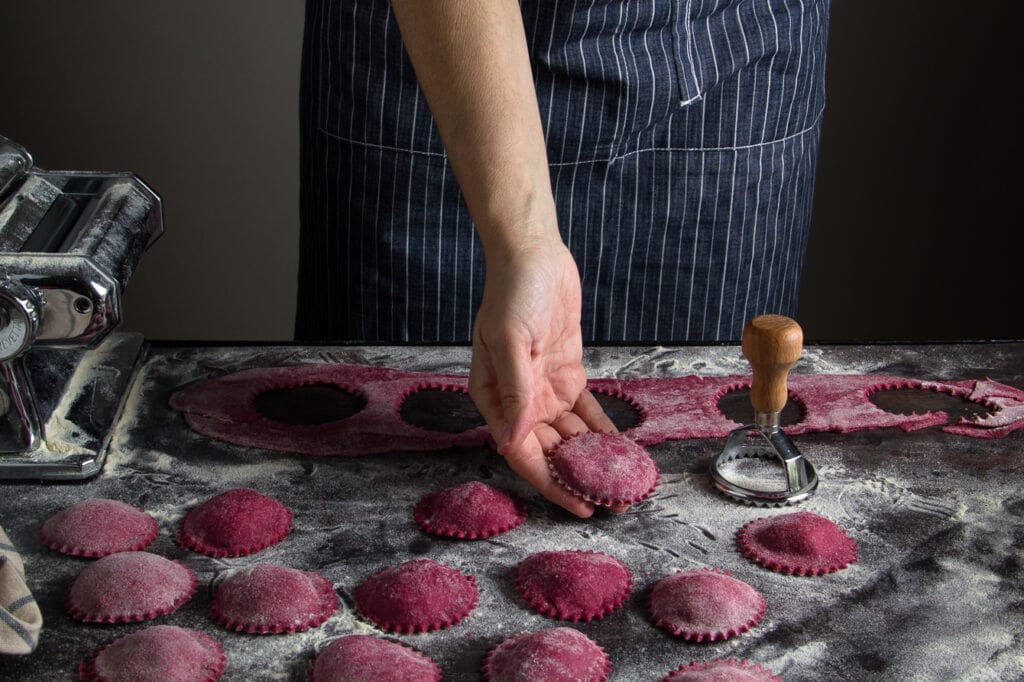 Homemade beetroot ravioli, filled with spinach and stamnotyri with black truffle, served with chives and red grapefruit zest