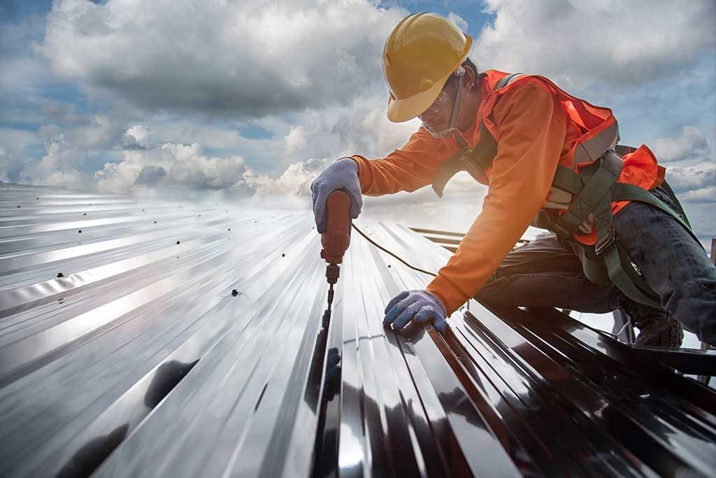 Commercial roofing contractor working on metal roofing
