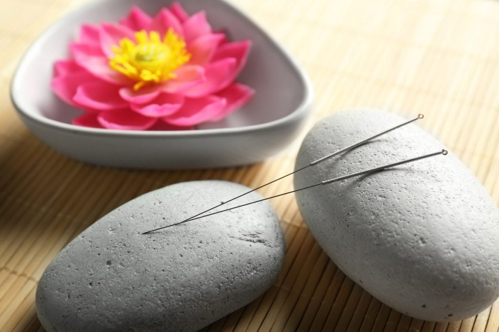 Acupuncture needles with stones and floating pink lotus blossom on bamboo mat