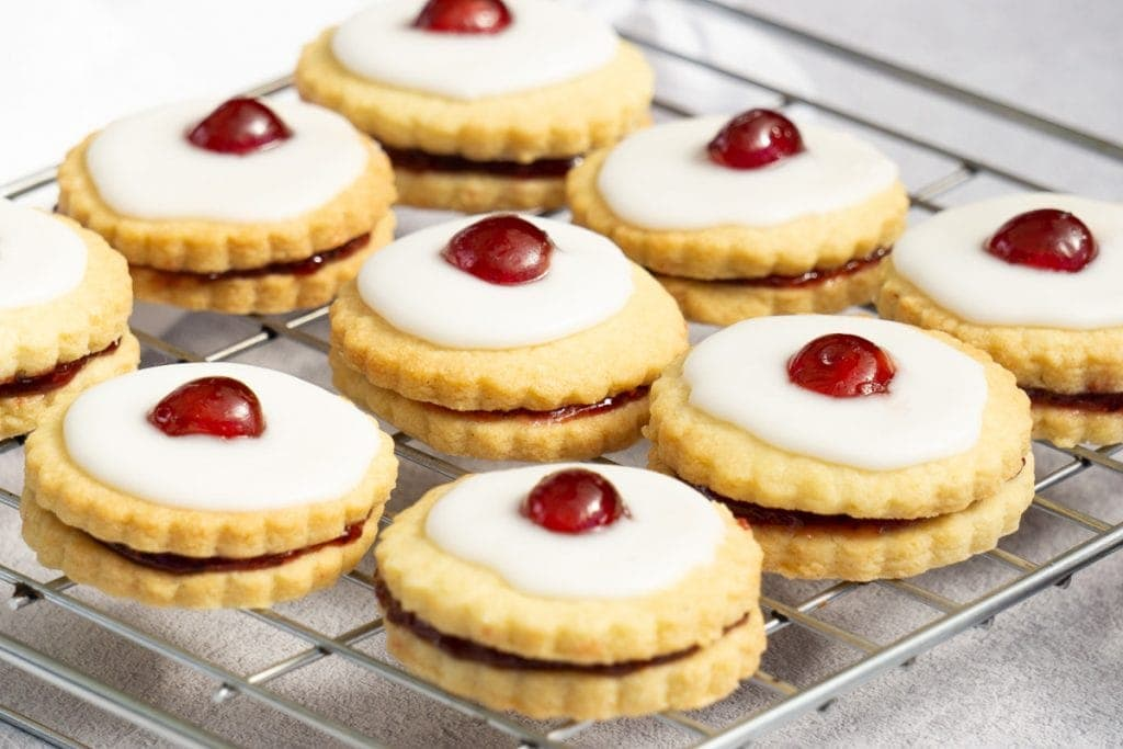 Scottish Empire Biscuits on a rack - Shortbread sandwiched with jam, iced and with a cherry on top