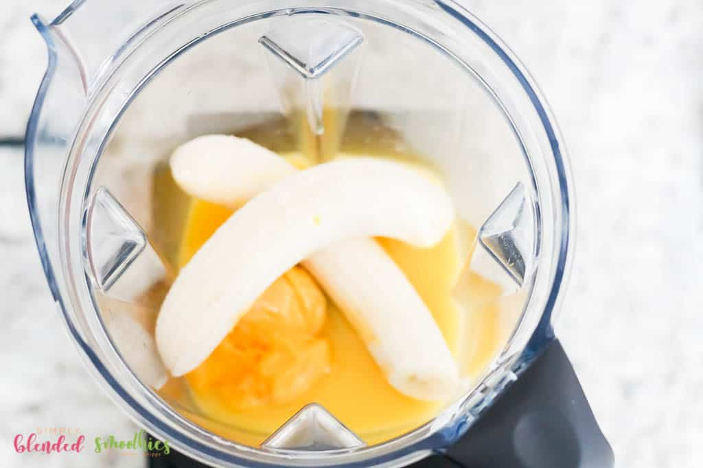 orange juice and orange juice concentrate and bananas in a blender from the top looking down into a blender