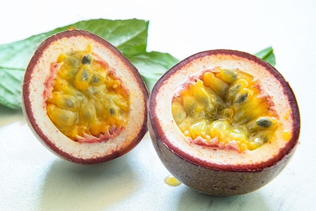 close up of dark-skinned passionfruit halfed to shoe juicy interior of this exotic tropical fruit