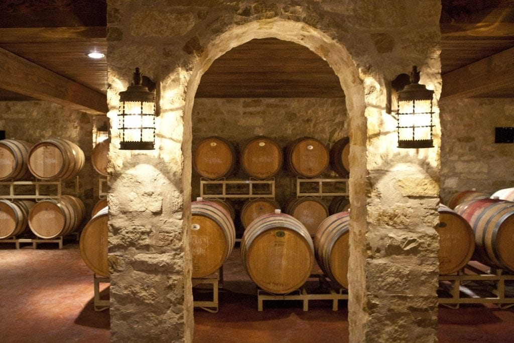 Barrel room of light-colored stone that looks like limestone, romantic lights, barrels of Texas red wine are readt for wine tasting in Texas