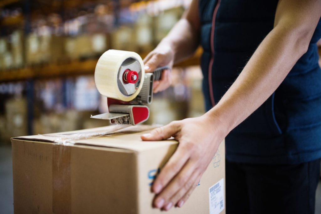 Man working in a contract packaging warehouse sealing a cardboard box