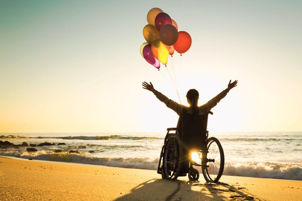 Une personne en fauteuil roulant, heureuse sur la plage avec un lancé de ballon