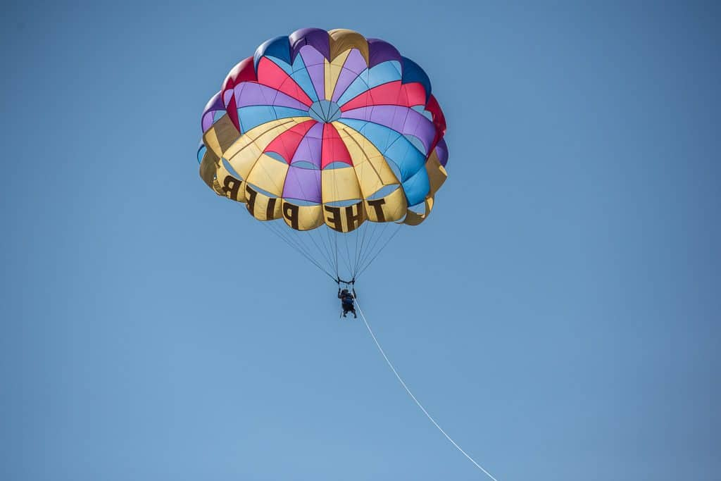 Brooke up in the sky during her Parasailing adventure with Inn at the Pier