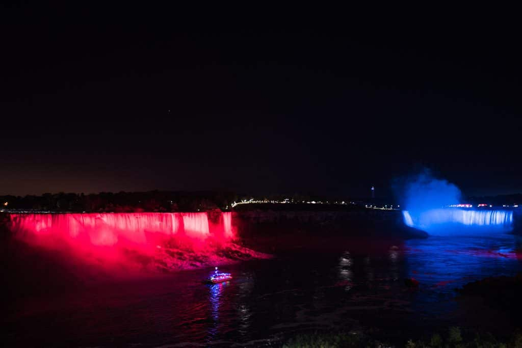 Niagara Falls lit in red and blue at night