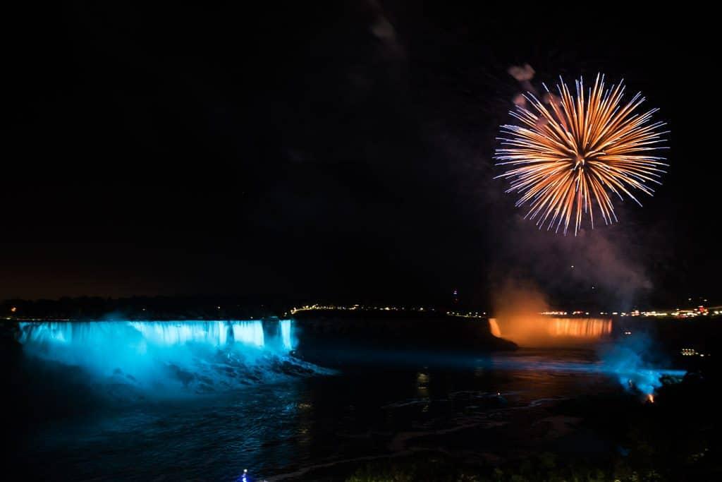 Blue and Orange Firework over a Blue and Orange Niagara Falls at night