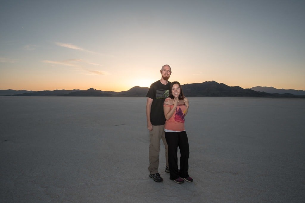 Brooke and Buddy on the bonneville salt flats as the sun sets behind the mountains behind them