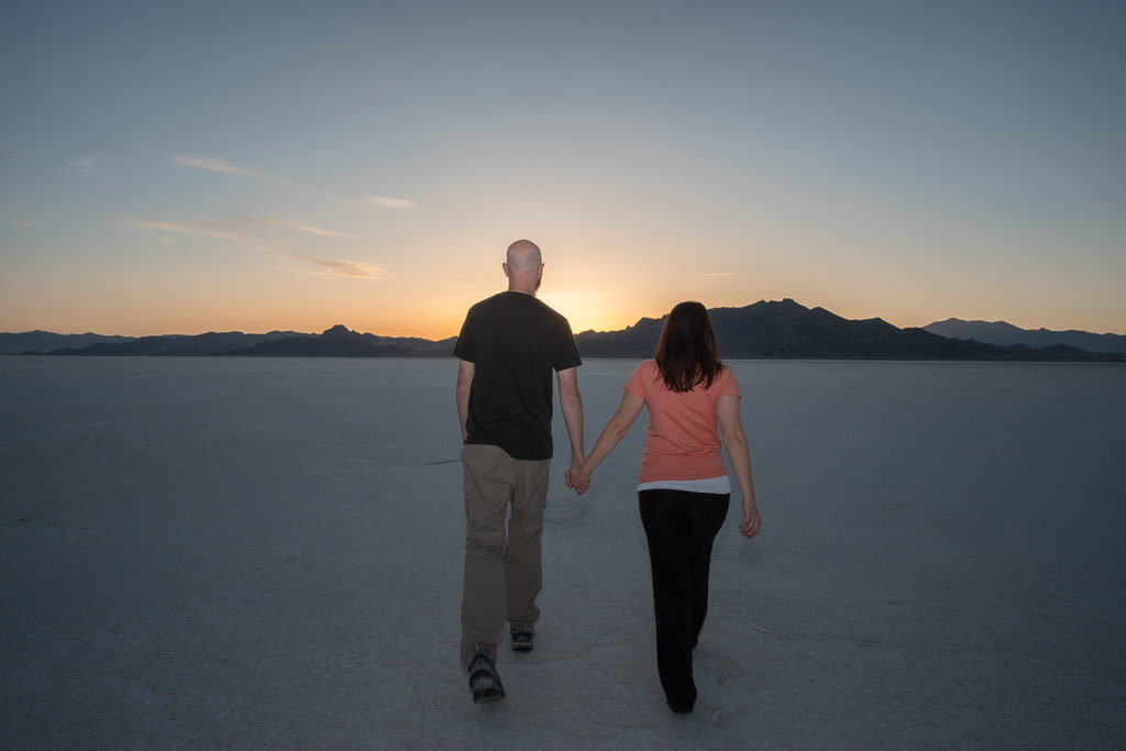 Brooke and Buddy hand-in-hand walking on the Bonneville Salt Flats during sunset