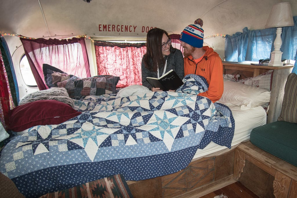 Brooke and Buddy sitting in the bed of The Ripple while reading the guest book and laughing