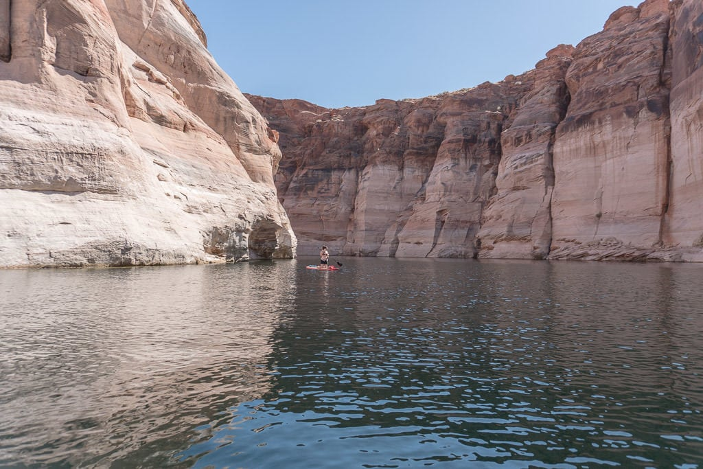 Brooke Paddleboarding on Lake Powell between giant rock cliffs on the way to Antelope Canyon in Page Arizona