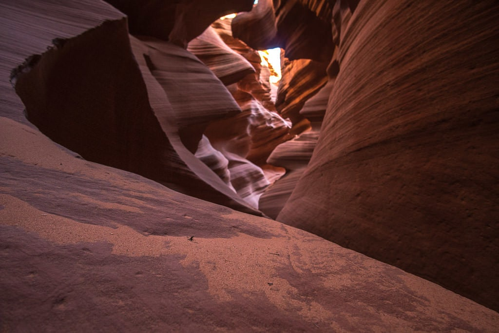 Some of the very fine sand in Lower Antelope Canyon on a rock looking back into the narrow slot canyon