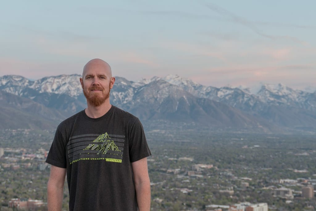 Buddy on the top of Ensign Hill with the mountains behind him and he is wearing a shirt with a mountain on it.