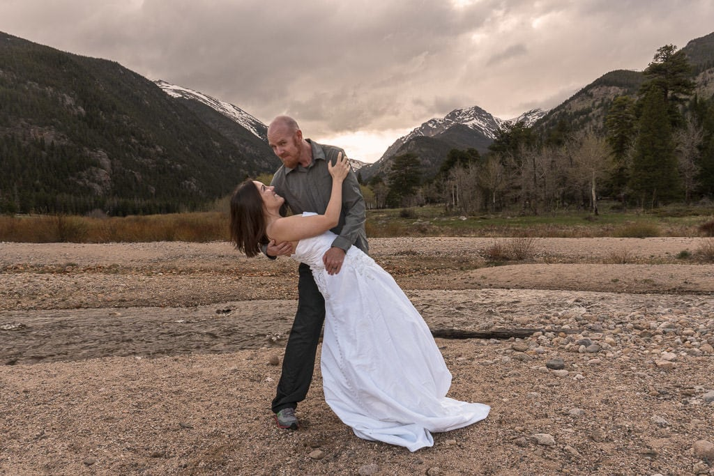 couple dipping in front of mountains on rocky mountain vow renewal