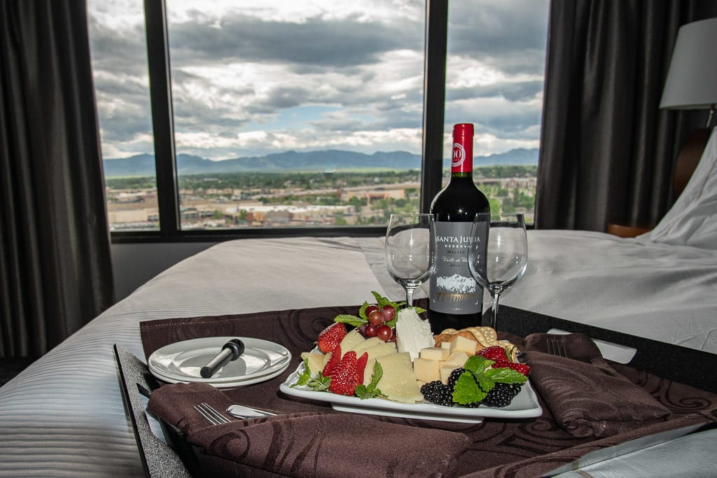 Cheese and fruit plate with a bottle of wine on our bed and a beautiful mountain scene out the large windows at the Westin Hotel in Westminster