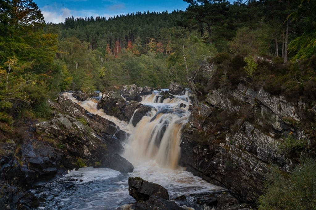 The powerful and large Rogie Falls with some trees in the background changing color with the autumn season
