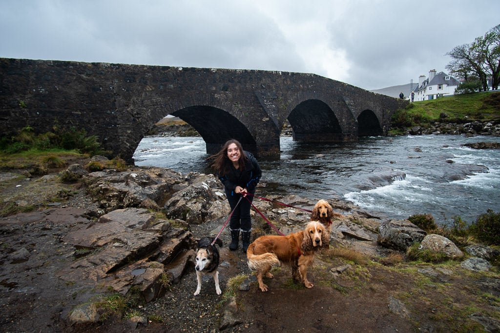 Brooke with the 3 dogs we were watching next to a river by a bridge outside of the Isle of Skye