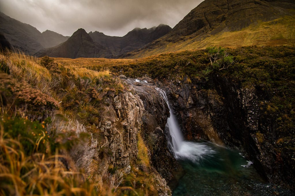 Waterfall with a dramatic mountainous scene behind it at Fairy Pools in Isle of Skye