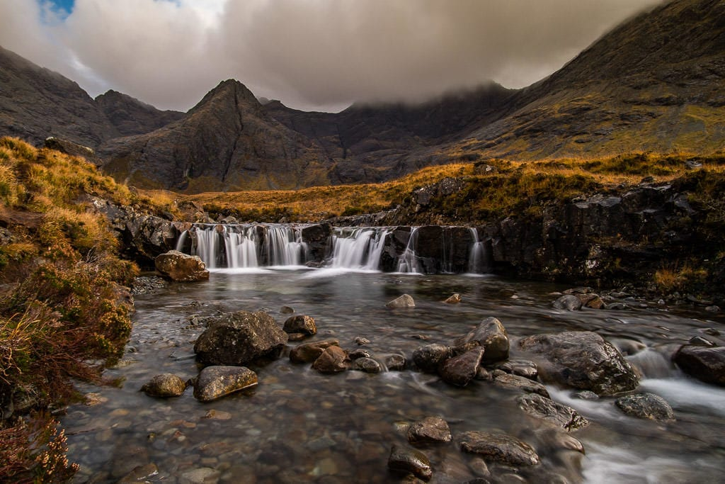 Waterfall with a dramatic mountainous scene behind it at Fairy Pools in Isle of Skye, our favorite place in Isle of Skye