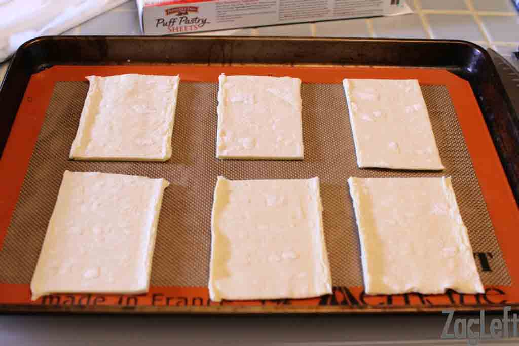 Puff pastry cut into six squares on a baking tray