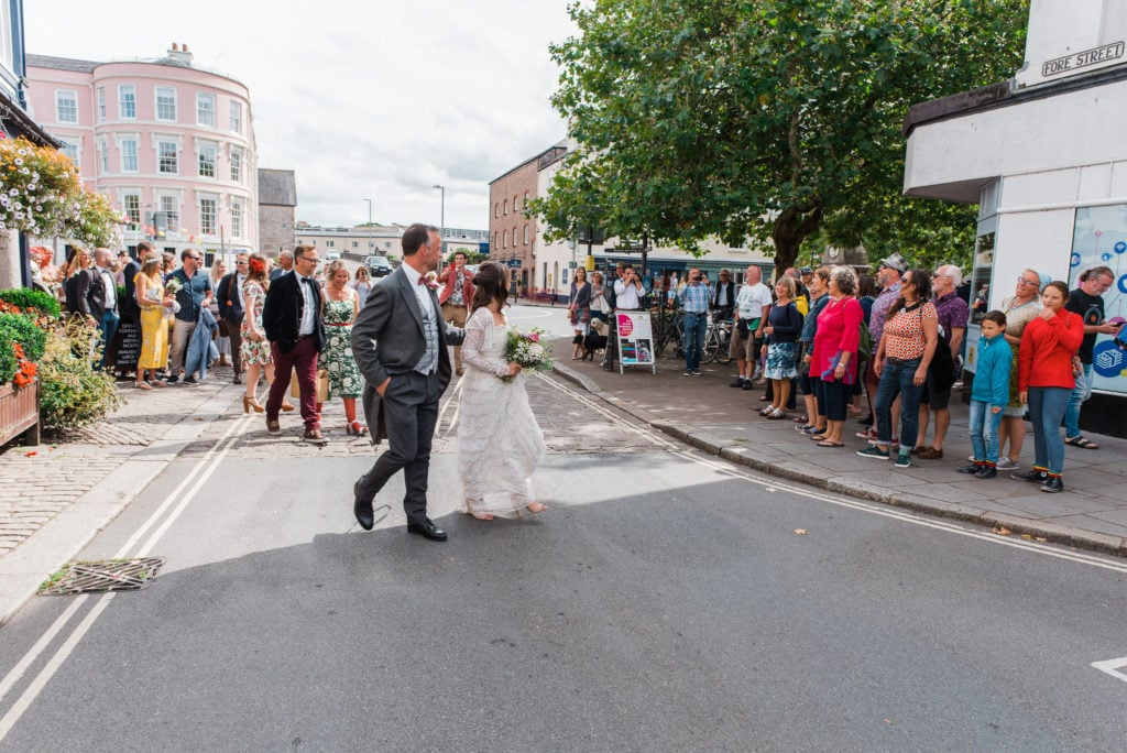 Bride and groom begin to lead procession of wedding party up Totnes high street