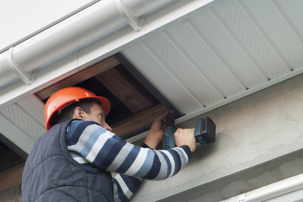 A Roofing Contractor mounts a soffit underneath the roof eaves