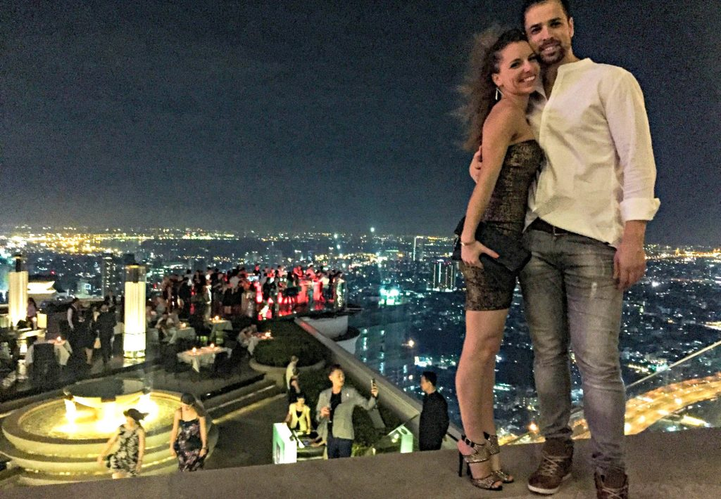 woman in high heels and short dress stands hugging man next to edge of deck overlooking a section of Sky Bar Bangkok and city lights below